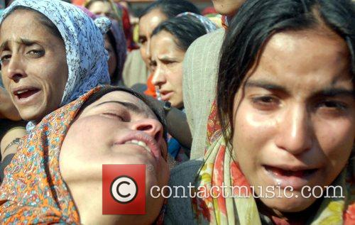 Kashmiri Muslim women weep during the funeral of...