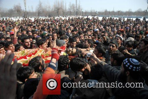 Kashmiri villagers carry the body of Nazir Ahmed,...