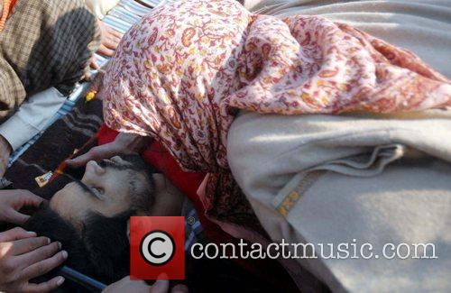 Kashmiri villagers embraces the body of Nazir Ahmed,...
