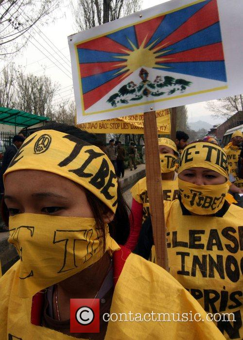 Tibetan exiles wear masks and hold placards...