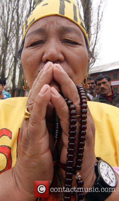 A Tibetan exile prays as demonstrators march through...