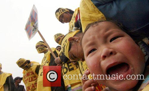 A Tibetan child cries and other protestors hold...