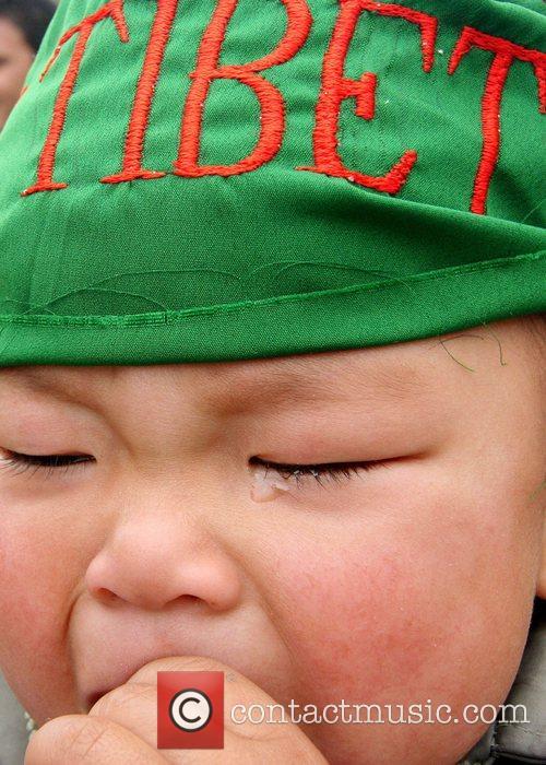 A Tibetan child cries as demonstrators march through...