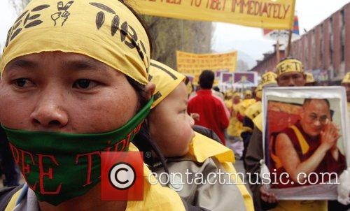 Tibetan exiles wear masks and hold pictures of...