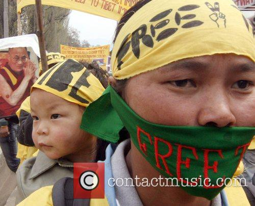 Tibetan exiles wear masks  as they march...