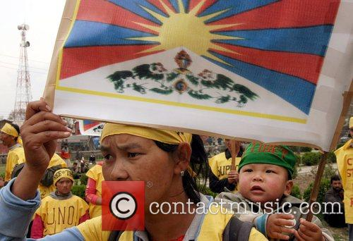 Tibetan exiles hold aloft the Tibetan flag as...