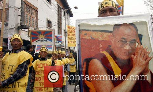 Protesters hold pictures of the Dalai Lama...