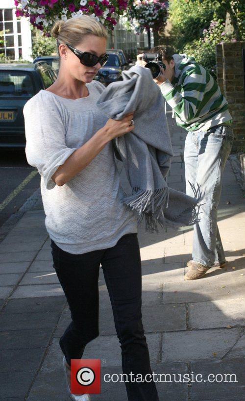 Kate Moss hides her face from the cameras...