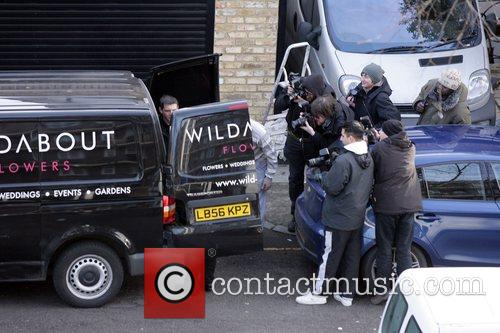 Photographers gather round a flower delivery van whilst...