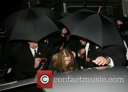 Kate Moss covered with umbrellas by bouncers even...