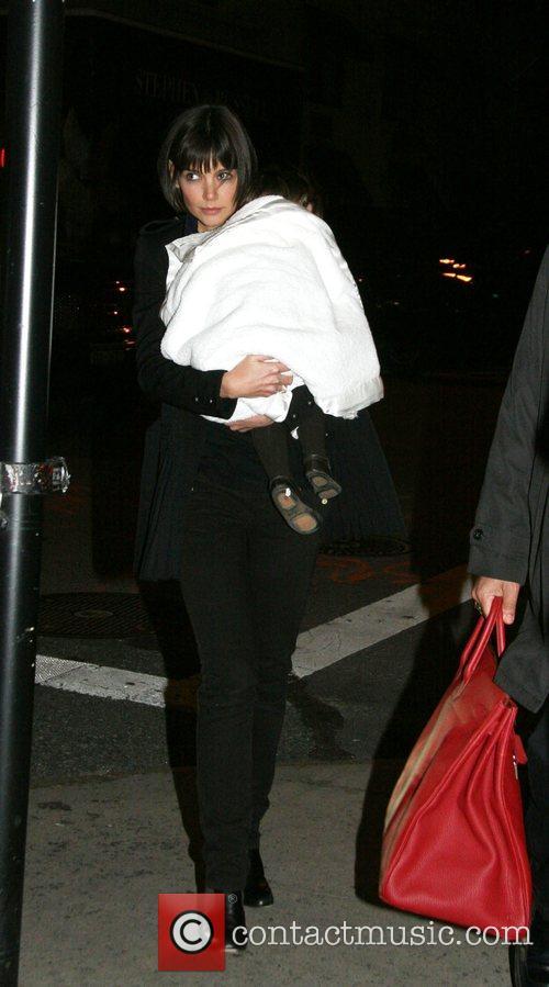 Walks through Manhattan carrying her daughter Suri wrapped...