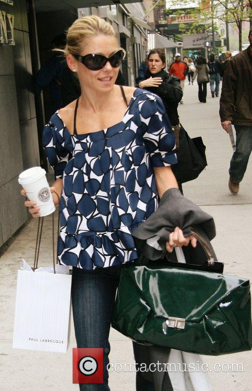 Kelly Ripa carrying a large coffee, waits for...