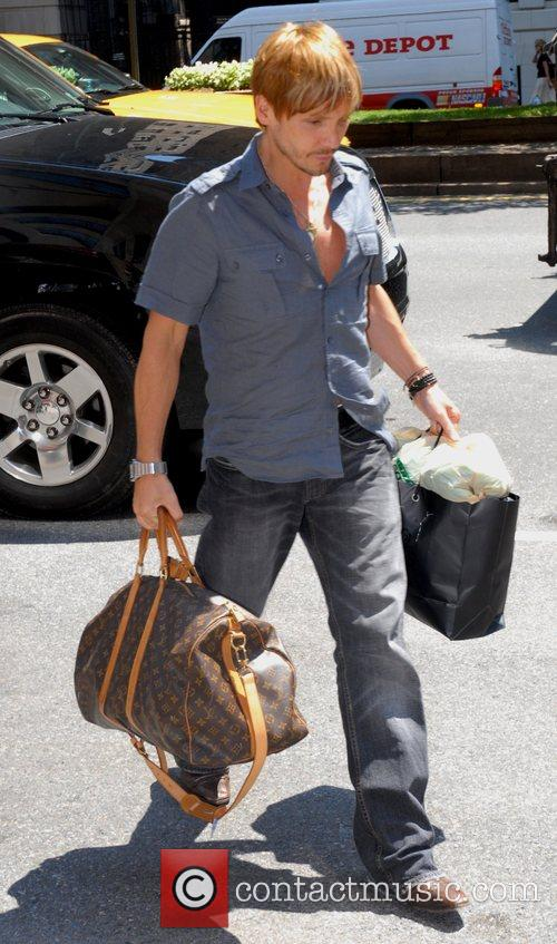 Ken Paves carrying his luggage as he checks...