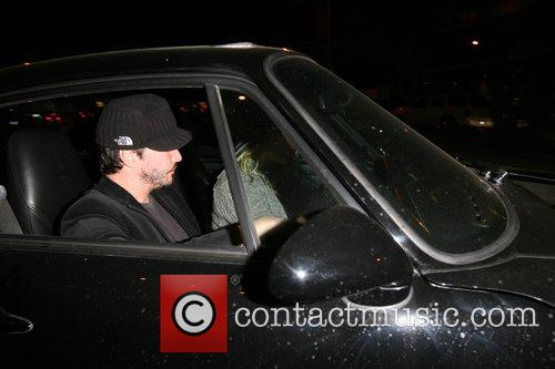 Keanu Reeves tries to avoid photographers as he...
