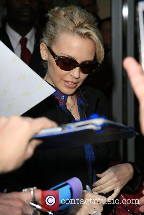 Is greeted by fans and autograph hunters as...