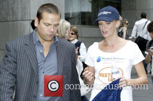Lachlan Murdoch walks his perspiring wife Sarah Murdoch...