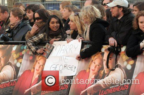 Fans hold up a sign which reads: Marry...