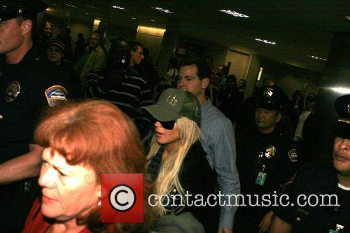 Lindsay Lohan is escorted through LAX airport by...