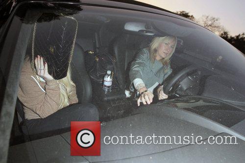Lindsay Lohan hides behind her handbag while her...