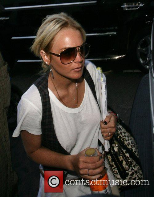 Lindsay Lohan arrives at a studio carrying a...
