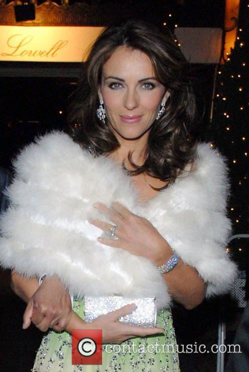Elizabeth Hurley wearing a white fur wrap as...
