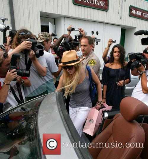 Lindsay Lohan wearing a straw hat is swamped...