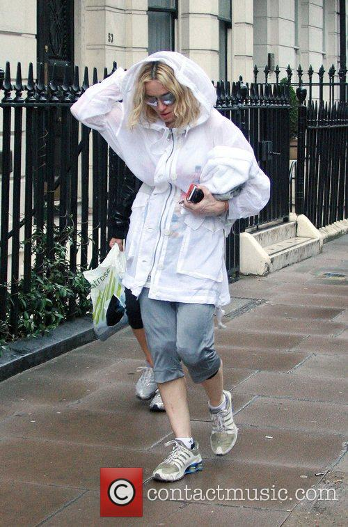 Madonna braves the rain to go to her...