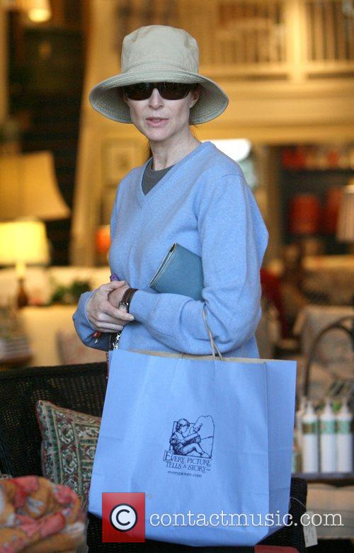 Marcia Cross wearing a big hat and very...