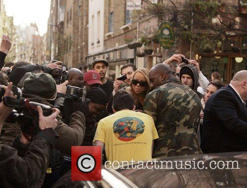 Mariah Carey getting swarmed by paparazzi photographers as...