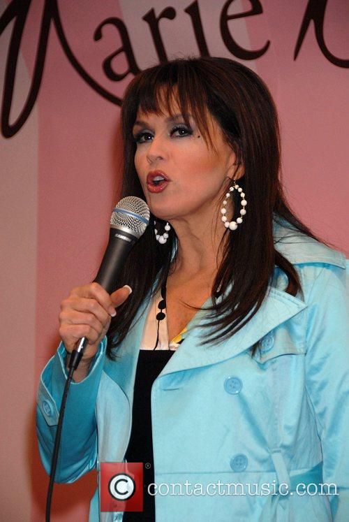 Marie Osmond signs her doll from the Marie...