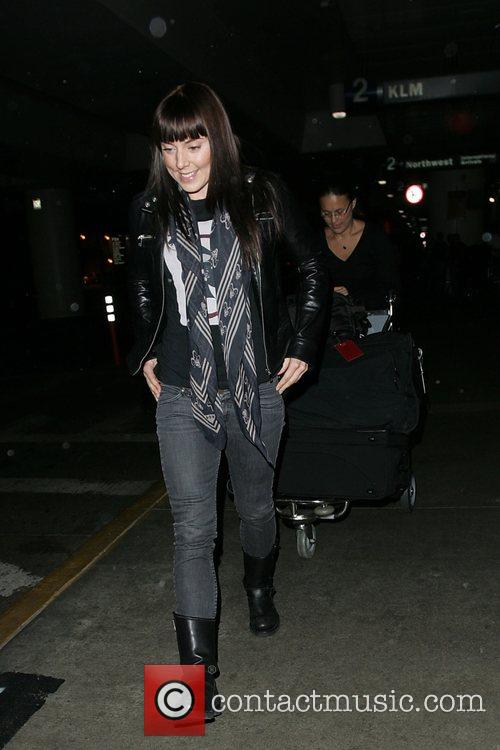 Arrives at LAX airport looking surprisingly cheery after...
