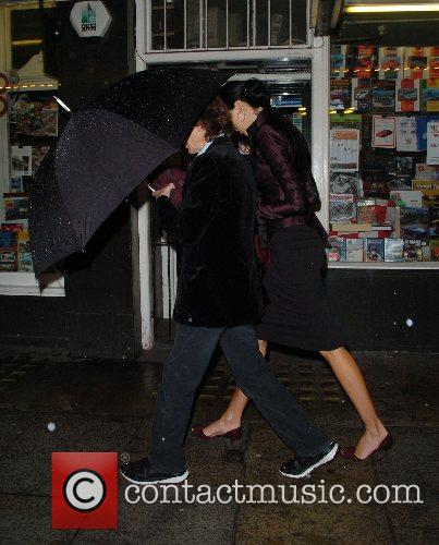 Mick Jagger carries an enormous umbrella while leaving...