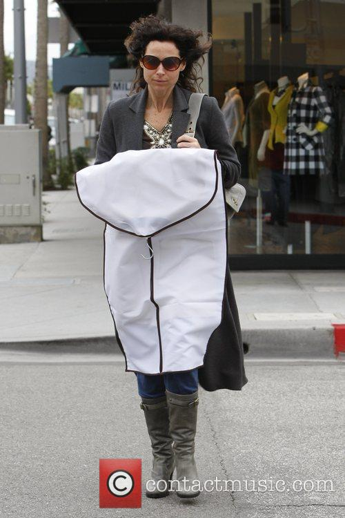 Minnie Driver holding a garment bag from 'Feraud'...