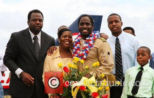 Barrington Irving, 23, (center) poses with family after...