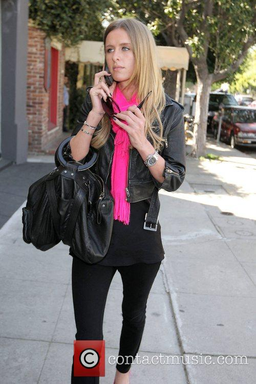 Nicky Hilton talks into her cellphone while out...