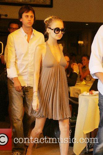 Nicole Richie hides her growing belly under a...