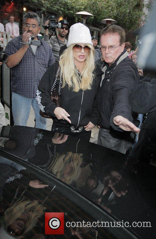 Is surrounded by paparazzi when leaving The Ivy...