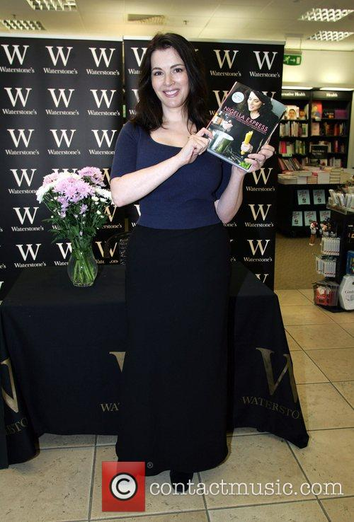 Signs copies of her new book 'Nigella Experss'...