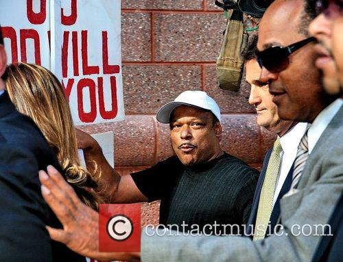 O.J. Simpson hurriedly pushes his way through the...
