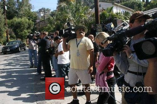 Reporters gather outside as Paris Hilton is escorted...