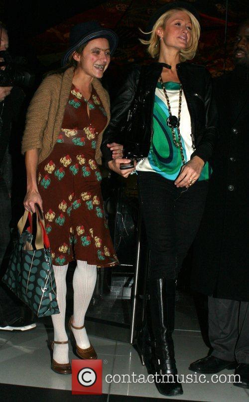 Paris Hilton laughing with a friend when arriving...