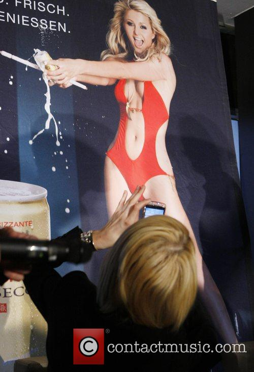 Paris Hilton taking a picture of her poster...