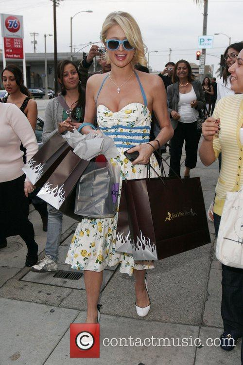 Paris Hilton carrying shopping bags while spending the...
