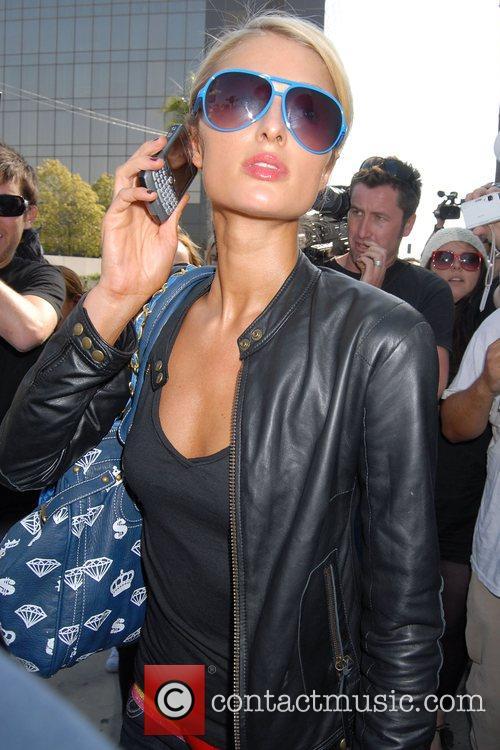Paris Hilton talks into her cellphone as she...