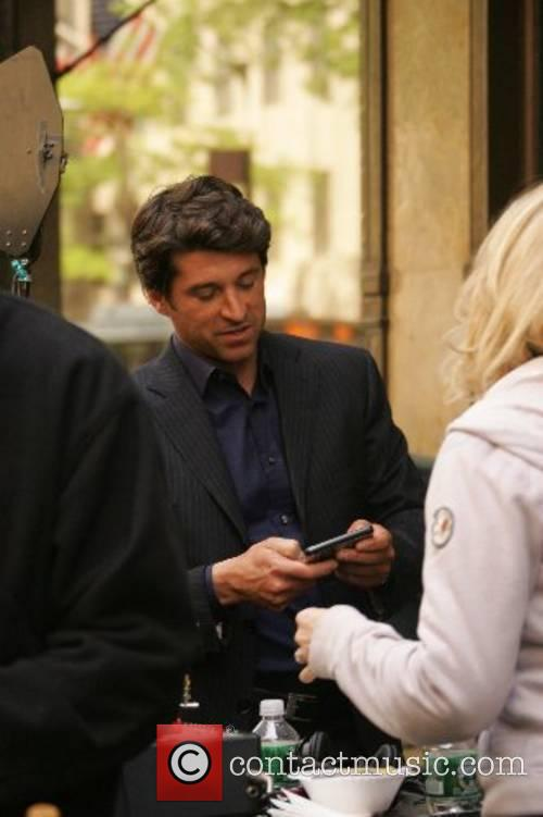 Patrick Dempsey sends a text on his mobile...