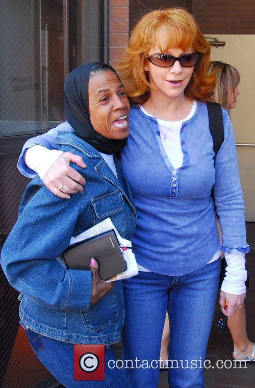 Reba McEntire poses with a fan while out...