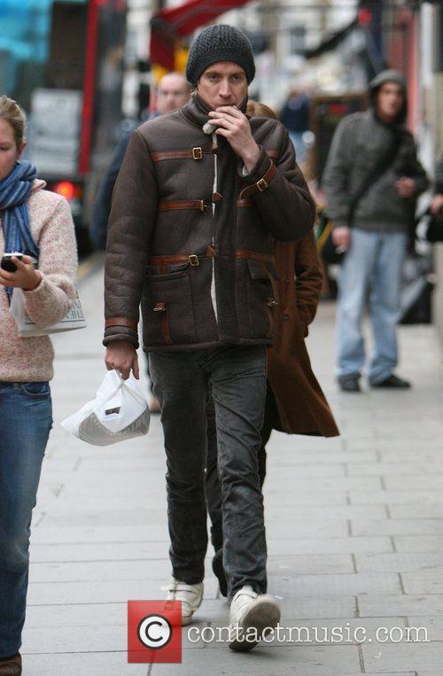Sienna Miller hides behind boyfriend Rhys Ifans to...
