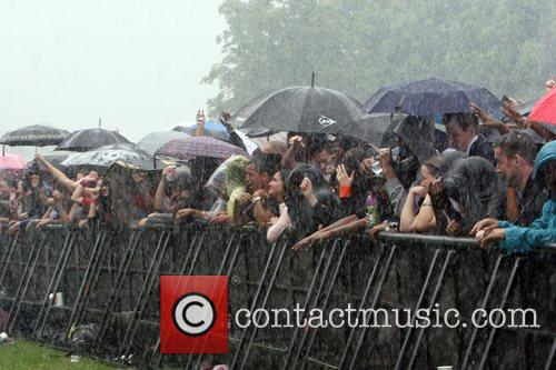 Crowd in the rain with umbrellas Rise Festival...