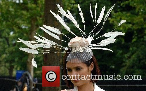 A racegoer wears an elaborate feathered hat for...