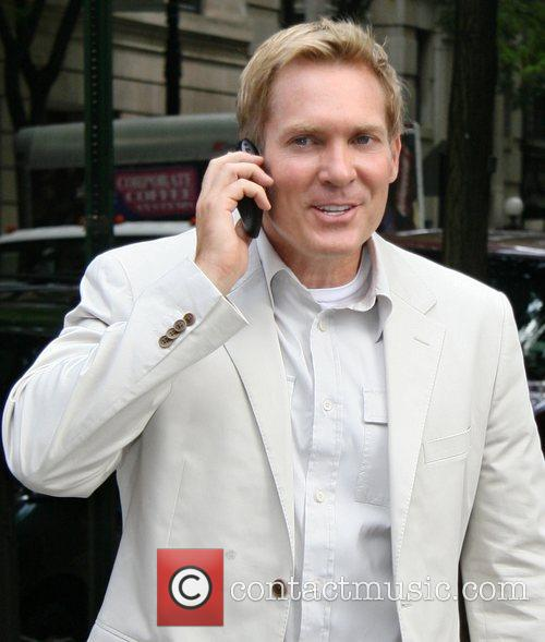 ABC's Meteorologist Sam Champion talking on his cell...